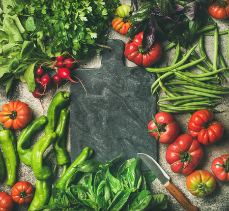 Healthy seasonal food cooking background. Flat-lay of fresh vegetables and greens over grey concrete background, black board in center, top view, copy space. Clean eating, vegan food preparation