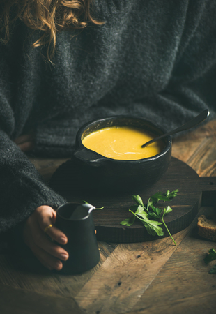 Woman in dark grey winter sweater eating sweet corn and shrimp chowder soup from black bowl. Autumn or winter warming food