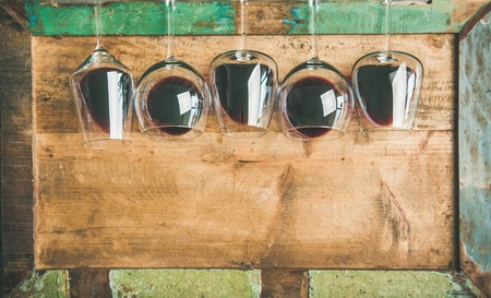 Flat-lay of red wine in glasses in row over rustic wooden tray background, top view, copy space. Wine bar, winery, wine tasting concept