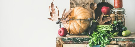 Autumn seasonal food ingredients, kitchen utensils. Vegetables, pumpkin, apples, canned food, fallen leaves over rustic chest of cupboard, copy space, wide composition. Thanksgiving dinner preparation