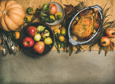 Thanksgiving dinner table. Flat-lay of roasted chicken or turkey, autumn fruit, pumpking, cutlery,leaves decoration over yellow linen table runner on grey concrete background, top view, copy space Stock Photo