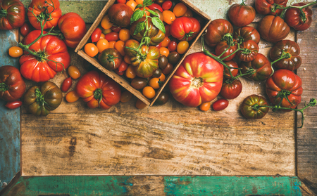 Flat-lay of fresh colorful ripe Fall or Summer heirloom, bunch and cherry tomatoes veriety over rustic tray background, top view, copy space. Local market seasonal produce Stock Photo