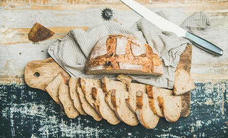 Flat-lay of freshly baked sourdough wheat bread loaf halved and cut in slices over linen napkin and rustic wooden table background, top view Stock Photo