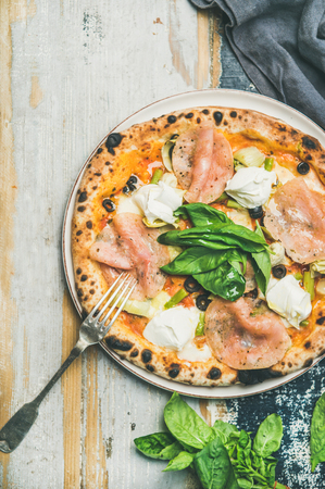 Italian lunch or dinner. Flat-lay of freshly baked pizza with artichokes, smoked turkey ham, olives, cream cheese, green basil leaves on plate over rustic wooden background, top view