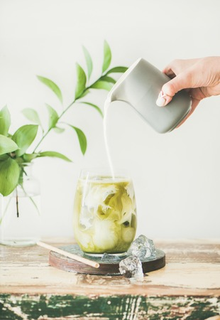 Iced matcha latte drink in glass with coconut milk pouring from pitcher by womans hand, white wall and plant branches at background, copy space. Summer refreshing beverage cold drink 版權商用圖片 - 108883858