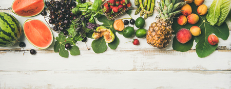 Summer food background. Flat-lay of seasonal fruit, vegetables and greens over white wooden background, top view, copy space, wide composition. Vegetarian, vegan, dieting, clean eating ingredients