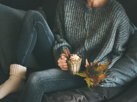 Woman in woolen sweater and jeans sitting and holding mug with hot chocolate or coffee with whipped cream and cinnamon and fallen leaf. Fall warming sweet drink Stockfoto