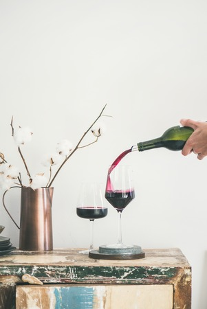 Red wine pouring from bottle into wineglass over rustic kitchen countertop, white background behind, copy space, vertical composition. Wine shop, winery, bojole nouveau holiday concept 写真素材 - 109273203