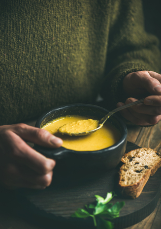 Man in dark green winter sweater eating sweet corn and shrimp chowder soup from black bowl with toasted bread, close-up. Autumn or winter warming food