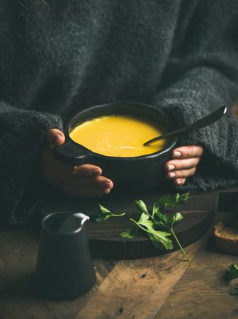 Woman in dark grey woolen winter sweater eating sweet corn and shrimp chowder soup from black bowl. Autumn or winter warming food