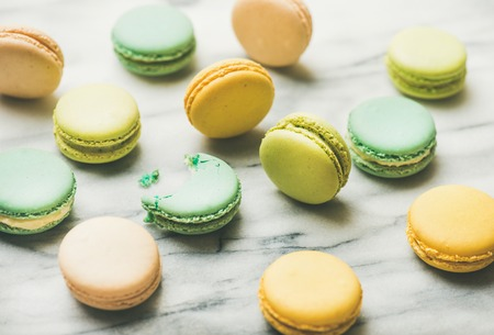 Sweet colorful French macaroon cookies over grey marble background, selective focus, horizontal composition Stock Photo