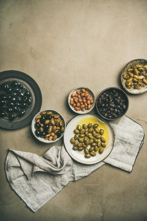 Flat-lay of various kinds of Mediterranean pickled olives in plates