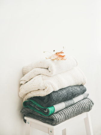Pile of knitted warm grey and white blankets, scarves and sweaters for winter or fall cold weather on white stool near white wall, copy space. Cosy home winter or Autumn atmospere