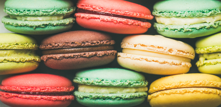 Flat-lay of sweet colorful French macaroon cookies stacked in rows