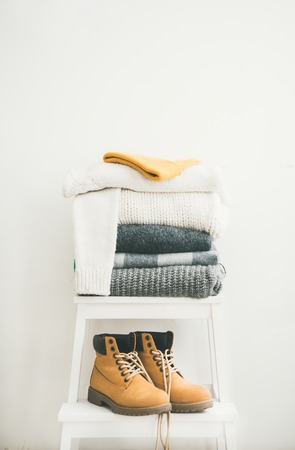 Pile of knitted warm grey and white blankets, scarves and woolen sweaters, cap and boots for winter or fall cold weather on white stool near white wall, copy space. Cosy home winter or Autumn atmospere