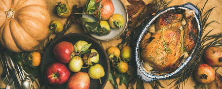 Thanksgiving dinner table. Flat-lay of roasted chicken or turkey, fruit, pumpkin, cutlery, leaves over yellow table runner on grey concrete background, top view, wide composition