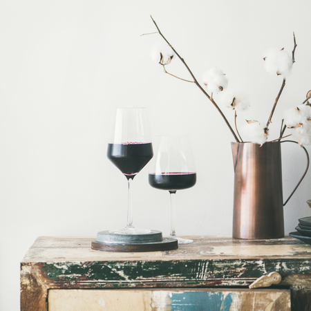 Two glasses of red wine and flowers over rustic kitchen countertop Stock Photo