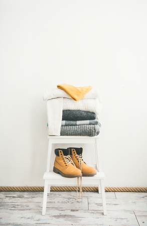 Pile of knitted warm grey and white blankets, scarves and sweaters, cap and boots for winter Stock Photo