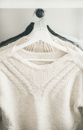 Row of warm knitted sweaters hanging on hangers for winter or fall cold weather, close-up. Stock Photo