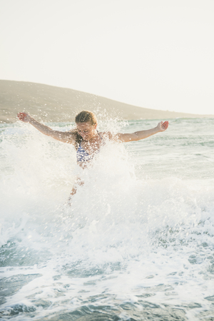 Young beautiful blond woman tourist in swimsuit standing and enjoying splash of wavy waters of Mediterranean sea in Prasonisi cape, Rhodes, Greece on summer day