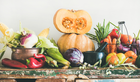 Fall vegetarian food ingredient variety. Assortment of various Autumn vegetables for healthy cooking over wooden rustic cupboard, white wall background. Local market organic produce Stock Photo