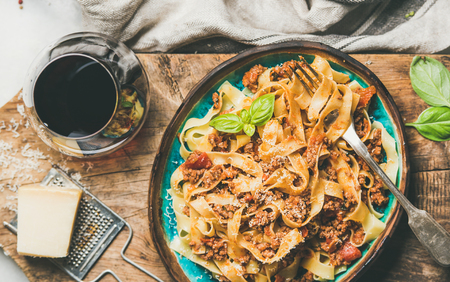 Italian traditional pasta dinner. Flat-lay of Tagliatelle bolognese with minced meat, tomato sauce and grated parmesan cheese and glass of red wine over rustic wooden board background, top view Banco de Imagens - 110730198