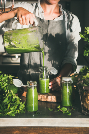 Making green detox take-away smoothie. Young female in linen apron pouring green smoothie drink from blender to bottle surrounded with vegetables and greens. Healthy, weight loss food concept Stok Fotoğraf
