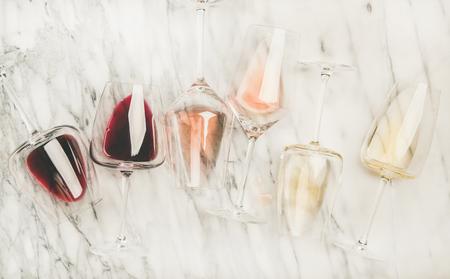 Flache Lage von Rot-, Rosen- und Weißwein in Gläsern und Korkenziehern über grauem Marmorhintergrund, Draufsicht. Bojole nouveau, Weinbar, Weingut, Weindegustationskonzept