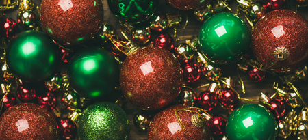 Christmas or New Year holiday background, texture, wallpaper. Flat-lay of colorful green, red and golden christmas tree decoration balls, top view, wide composition. New year greeting card concept 写真素材