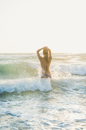 Young blond woman tourist in swimsuit standing backwards and enjoying wavy waters of Mediterranean sea in Prasonisi cape, Rhodes, Greece on summer day at sunset Stok Fotoğraf