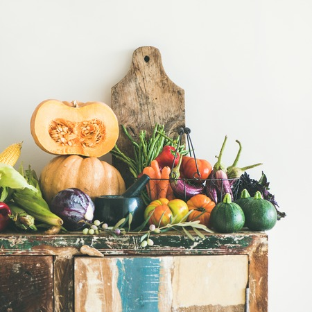 Fall vegetarian food ingredient variety. Assortment of Autumn vegetables for healthy cooking over rustic cupboard, white wall background, copy space, square crop. Local market organic produce