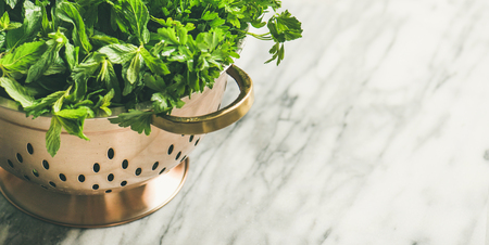 Bunch of fresh green garden herbs in brass colander over marble kitchen table, top view, copy space, horizontal composition