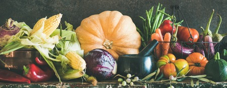 Fall vegetarian food ingredients. Assortment of various Autumn vegetables for healthy cooking over rustic cupboard, dark wall background, copy space, wide composition. Local market organic produce