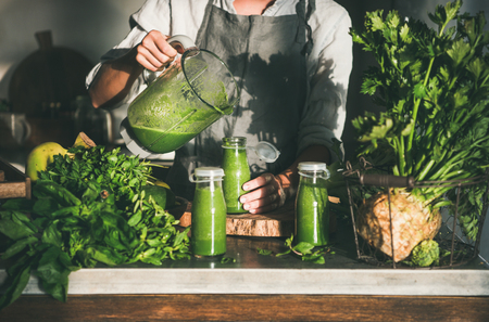 Making green detox take-away smoothie. Woman in linen apron pouring green smoothie drink from blender to bottle surrounded with vegetables and greens. Healthy, clean eating, weight loss food concept Фото со стока