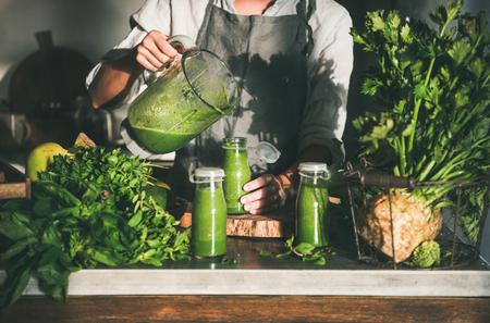 Preparare un frullato da asporto disintossicante verde. Donna in grembiule di lino che versa bevanda frullato verde dal frullatore alla bottiglia circondata da verdure e verdure. Mangiare sano e pulito, concetto di cibo per la perdita di peso