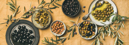 Flat-lay of various kinds of Mediterranean pickled olives in plates and bowls and olive tree branches on yellow linen cloth, top view, wide composition. Mediterranean meze appetizer
