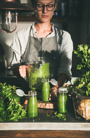 Making green detox take-away smoothie. Woman in linen apron and glasses pouring green smoothie drink from blender to bottle surrounded with vegetables and greens. Healthy, weight loss food concept Stok Fotoğraf