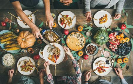 Fête traditionnelle de célébration du jour de Thanksgiving. Mise à plat d'amis ou de famille mangeant différentes collations et dinde à la table de Noël festive, vue de dessus
