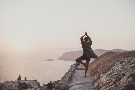 Young woman tourist standing and meditating on ancient stones of Monolithos castle in Rhodes island, Greece, at sunset on clear summer day