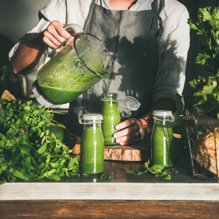 Making green detox take-away smoothie. Woman in linen apron pouring green smoothie drink from blender to bottle surrounded with vegetables and greens, square crop. Healthy, weight loss food concept