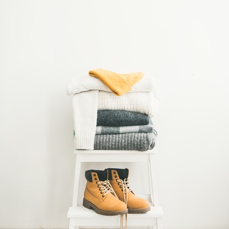 Pile of knitted warm blankets, scarves and sweaters, cap and boots for winter or fall cold weather on white stool near white wall, copy space, square crop. Cosy home winter atmospere