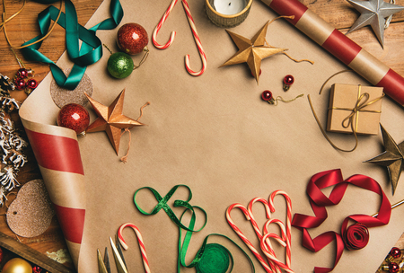 Getting ready for Christmas or New Year holiday. Flat-lay of decorations, ribbons, gift paper, door wreath, glittering balls, candy canes, top view, copy space. Christmas festive mood