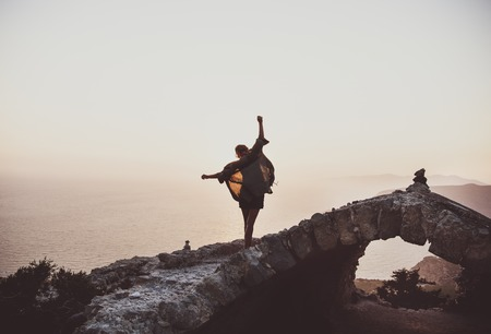 Young slim woman tourist balancing on stones of Monolithos castle in Rhodes island, Greece, at sunset on clear summer day