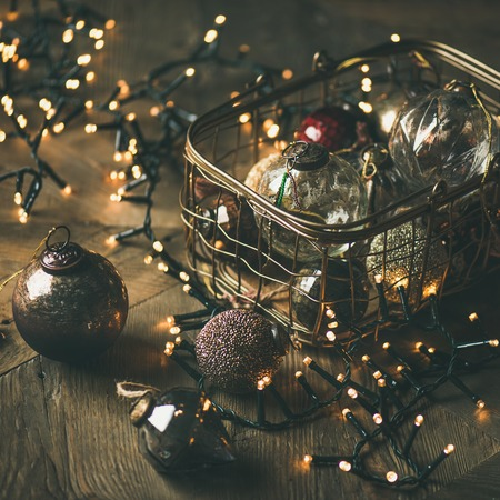 Christmas or New Year background, preparing for holiday. Christmas tree toy decoration balls in vintage box and light garland over rustic wooden background, selective focus, square crop