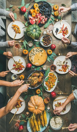 Thanksgiving, Friendsgiving holiday celebration. Flat-lay of friends feasting at Thanksgiving Day table with turkey, pumpkin pie, roasted vegetables, fruit, rose wine, top view, vertical composition