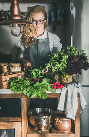 Fall seasonal vegetarian, vegan dinner cooking. Young woman in linen apron and glasses cutting herbs and vegetables on concrete kitchen counter. Slow food, comfort food, healthy diet, clean eating