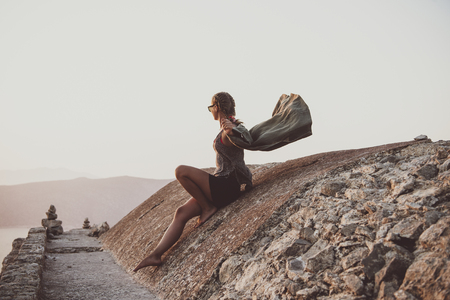 Young woman tourist sitting on ancient stones and looking at horizon in Monolithos castle in Rhodes island, Greece, at sunset on clear summer day