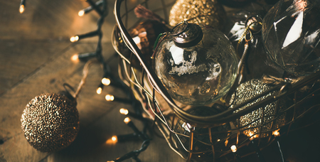 Christmas or New Year background. Vintage Christmas tree golden toy decoration balls in box and light garland over rustic wooden table background, selective focus 写真素材