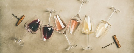 Flat-lay of red, rose and white wine in glasses and corkscrews over grey concrete background, top view, wide composition. Wine bar, winery, wine degustation concept Stock Photo
