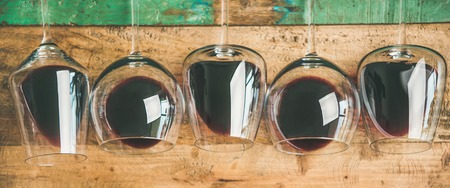 Flat-lay of red wine in glasses over rustic wooden tray background, top view, copy space, wide composition. Wine bar, winery, wine tasting concept